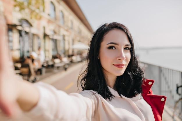 Pewna siebie biała kobieta z czarnymi włosami robi selfie z zainteresowanym wyrazem twarzy