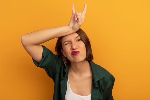 Pewna siebie całkiem kaukaska kobieta kładzie dłoń na głowie, wskazując rogi ręką znak na pomarańczowo