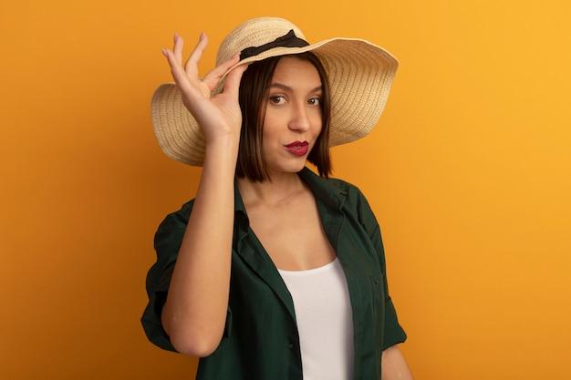 Pewna siebie całkiem kaukaska kobieta w kapeluszu plażowym kładzie rękę na kapeluszu na pomarańczowo