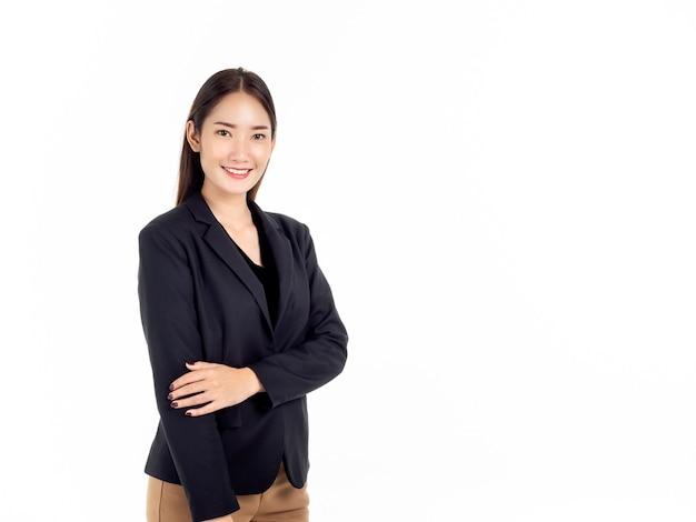 Pewna siebie, całkiem młoda azjatycka kobieta w czarnym garniturze z uśmiechem, stojąca z podwiniętymi rękami w skromny sposób