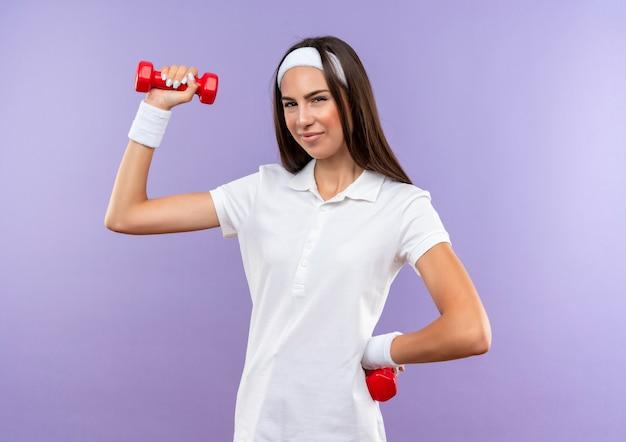 Pewna siebie, całkiem wysportowana dziewczyna nosząca opaskę i opaskę na nadgarstek trzymająca hantle izolowane na fioletowej ścianie