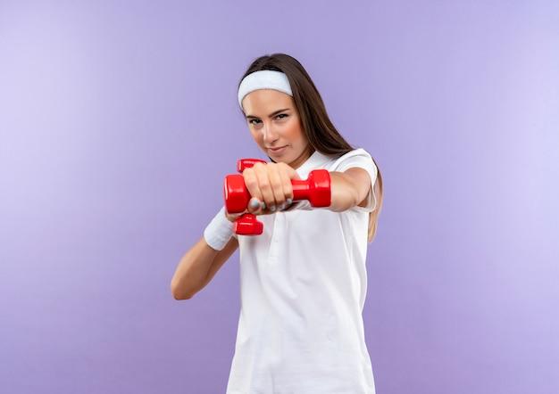 Pewna siebie, całkiem wysportowana dziewczyna nosząca opaskę na głowę i nadgarstek wyciągający hantle na fioletowej ścianie