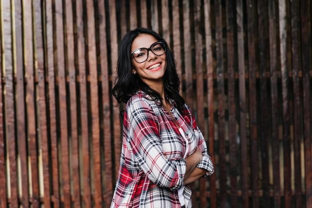 Pewna siebie ciemnowłosa kobieta pozuje z natchnionym uśmiechem. błogi brunetka dziewczyna w okularach stojący odkryty z rękami skrzyżowanymi.