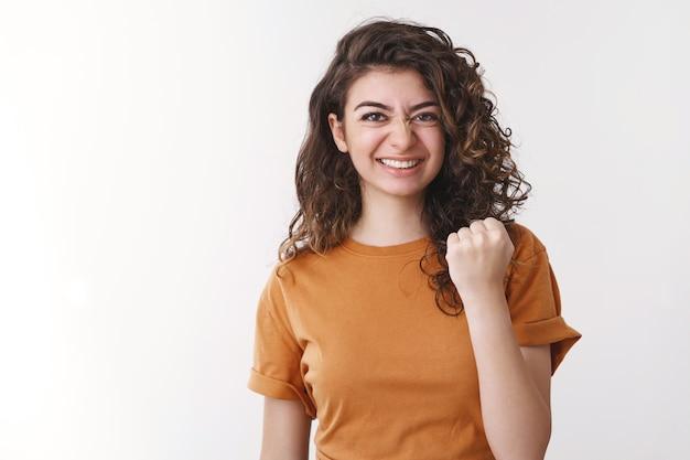 Pewna siebie, dobrze wyglądająca, zdeterminowana młoda kobieta w końcu osiągnęła triumf dziewczyny podekscytowany zaciskać podniesione pięści tak sukces gest uśmiechać czuć smak zwycięstwo wygrać, stojąc szczęście białe tło