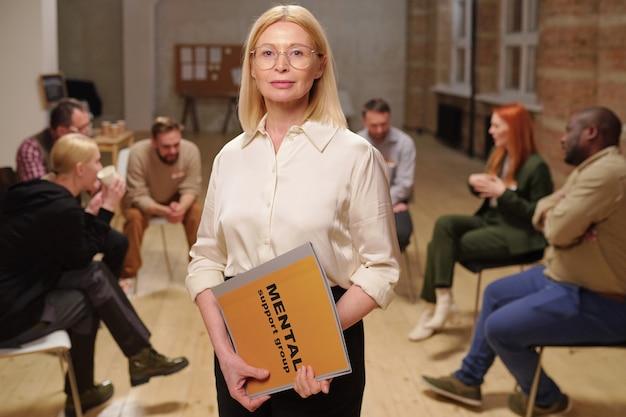 Pewna siebie dojrzała doradczyni w okularach i eleganckiej odzieży codziennej, prowadząca dziennik grupy wsparcia psychicznego, stojąc przeciwko pacjentom
