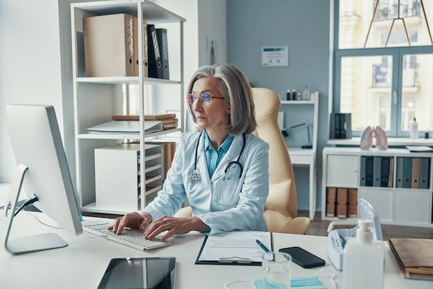 Pewna siebie, dojrzała lekarka w białym fartuchu laboratoryjnym, pracująca na komputerze, siedząc w swoim gabinecie