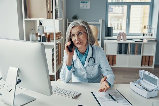 Pewna siebie dojrzała lekarka w białym fartuchu laboratoryjnym rozmawia przez telefon i uśmiecha się siedząc w swoim gabinecie