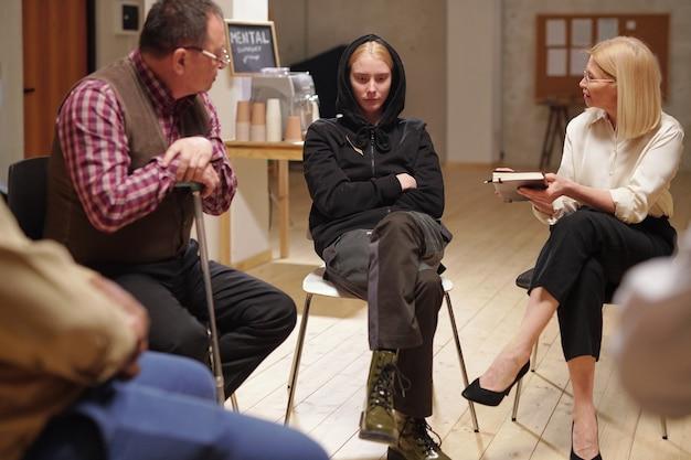 Pewna siebie doradczyni i dojrzały pacjent patrzący na zmartwioną dziewczynę siedzącą między nimi, podczas gdy psycholog udziela jej rad