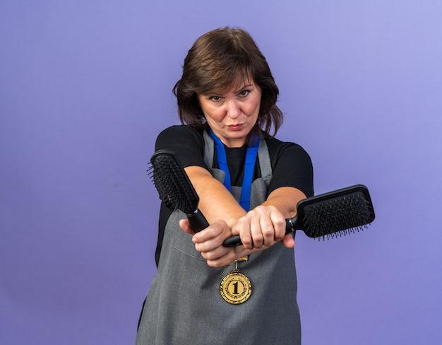 Pewna siebie dorosła fryzjerka w mundurze ze złotym medalem na szyi trzymająca grzebienie izolowane na fioletowej ścianie z miejscem na kopię