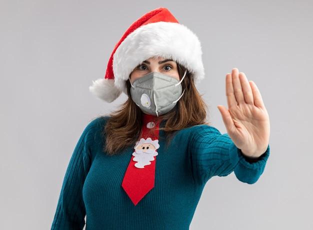 Pewna siebie dorosła kaukaska kobieta z czapką mikołaja i krawatem świętego mikołaja w masce medycznej gestykuluje znak stop ręki