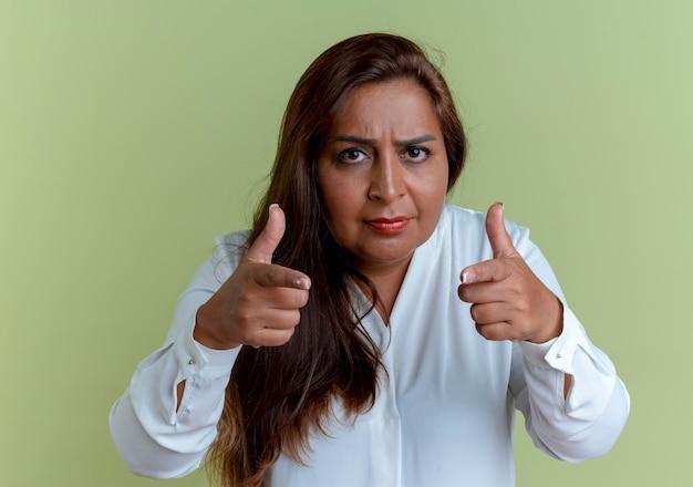 Pewna siebie dorywczo kaukaski kobieta w średnim wieku pokazuje gest na białym tle na oliwkowej zieleni