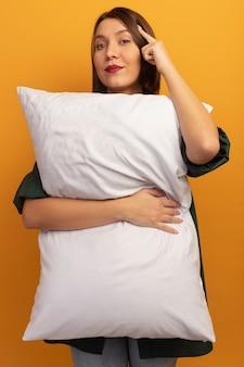 Pewna siebie dość kaukaska kobieta trzyma poduszkę i kładzie palec na skroni na pomarańczowo