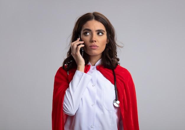 Pewna siebie dziewczyna superbohatera kaukaskiego w mundurze lekarza z czerwoną peleryną i stetoskopem rozmawia przez telefon patrząc z boku na białym tle na białej ścianie z miejscem na kopię