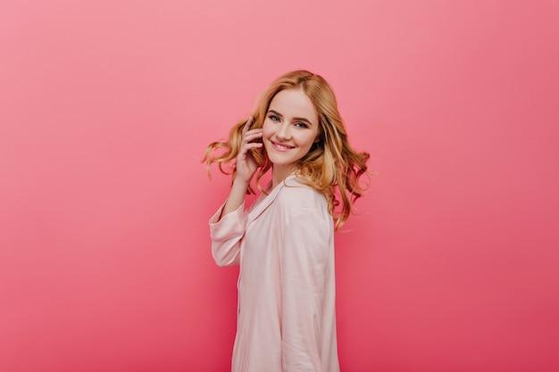 Pewna siebie dziewczyna w bawełnianej piżamie bawi się włosami. wewnętrzne zdjęcie wesołej modelki w jasnoróżowym kombinezonie nocnym.