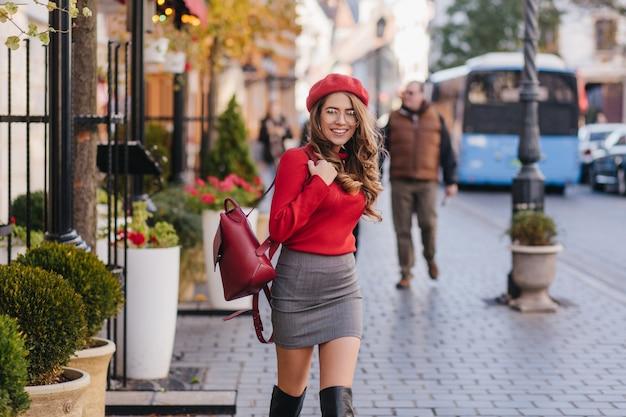 Pewna siebie dziewczyna w wysokich do kolan butach i krótkiej spódniczce idąc ulicą
