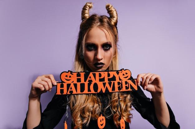 Pewna siebie dziewczyna z przerażającym czarnym makijażem pozuje przed imprezą. poważna blondynka w stroju wampira świętuje halloween.