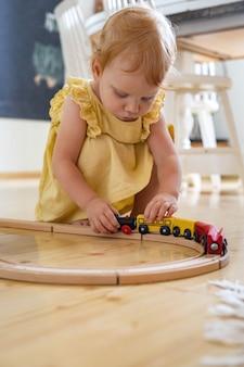 Pewna siebie dziewczynka w sukience grająca w drewniane pociągi koleje maria montessori materiały ekologiczne