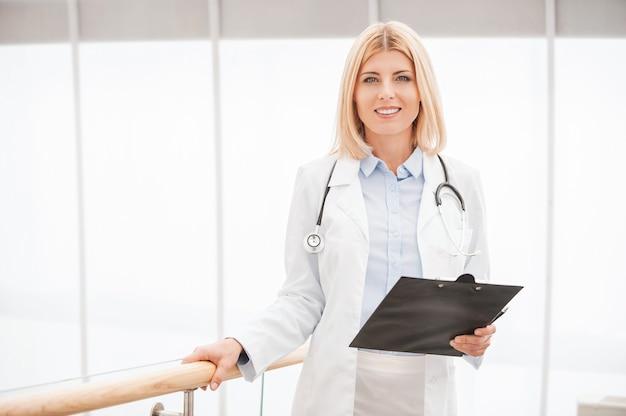 Pewna siebie i doświadczona lekarka. pewna lekarka w białym mundurze trzymająca schowek i uśmiechnięta