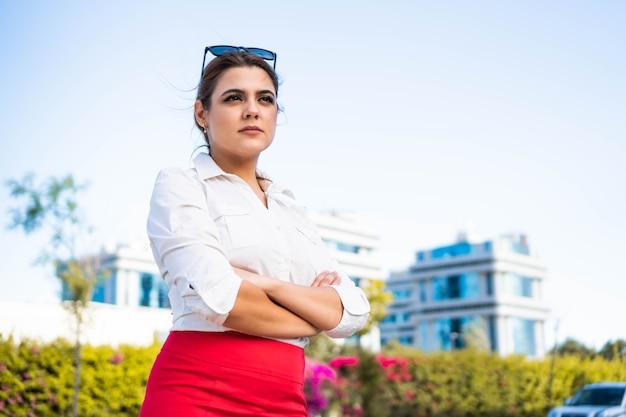 Pewna siebie i odnosząca sukcesy bizneswoman w swoim miejscu pracy na tle drapaczy chmur