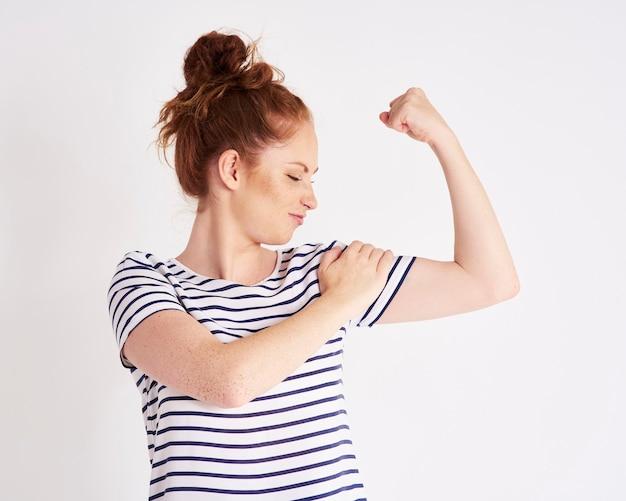 Pewna siebie i silna kobieta pokazująca swój strzał na biceps