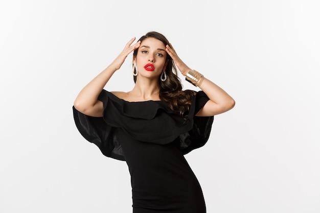 Pewna siebie i stylowa kobieta w czarnej eleganckiej sukni, patrząca elegancko w kamerę, stojąca na białym tle