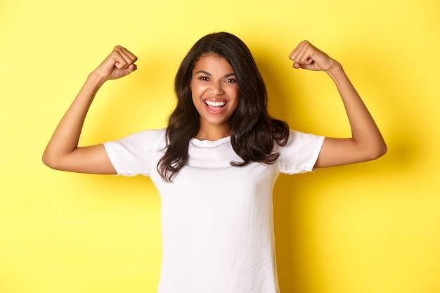 Pewna siebie i wesoła afroamerykańska dziewczyna napinająca bicepsy i uśmiechnięta, wyglądająca na silną i asertywną