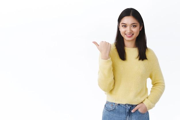 Pewna siebie i wesoła, piękna azjatycka brunetka w żółtym swetrze, przedstawiająca nowy produkt, wskazująca kciukiem w lewo, zapraszająca do obejrzenia wydarzenia lub kliknięcia banera promocyjnego, uśmiechnięta szczęśliwa, polecająca reklamę