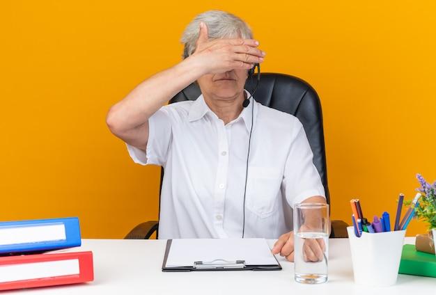 Pewna siebie kaukaska operatorka call center na słuchawkach siedząca przy biurku z narzędziami biurowymi trzymająca rękę przed oczami