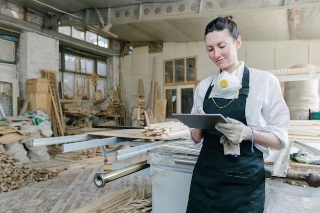 Pewna siebie kobieta pracująca jako stolarz we własnym warsztacie stolarskim.
