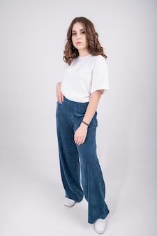 Pewna siebie kobieta w białej koszulce i spodniach z dżerseju palazzo. casualowa stylowa odzież dla młodej dziewczyny.