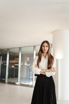 Pewna siebie kobieta w długiej czarnej spódnicy i białej bluzce, skrzyżowanymi rękami na piersi w pewnej siebie pozie.