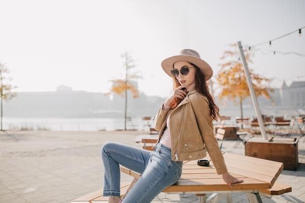 Pewna siebie kobieta w dżinsowych spodniach siedzi na stole w kawiarni ulicy