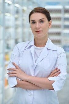 Pewna siebie kobieta w fartuchu laboratoryjnym w aptece