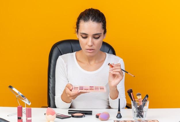 Pewna siebie ładna kaukaska kobieta siedzi przy stole z narzędziami do makijażu, trzymając pędzel do makijażu i patrząc na paletę cieni do powiek