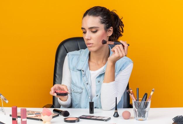 Pewna siebie, ładna kaukaska kobieta siedzi przy stole z narzędziami do makijażu, trzymając pędzel do makijażu, patrząc na rumieniec