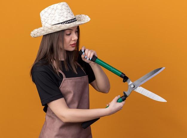 Pewna siebie ładna kaukaska ogrodniczka w kapeluszu ogrodniczym, trzymająca i patrząca na nożyczki ogrodnicze