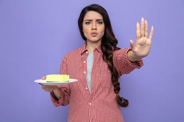 Pewna siebie ładna kaukaska sprzątaczka trzymająca gąbkę na talerzu i wskazująca znak stop ręką