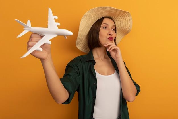 Pewna siebie ładna kobieta w kapeluszu plażowym kładzie rękę na twarzy i trzyma model samolotu patrząc na bok na białym tle na pomarańczowej ścianie