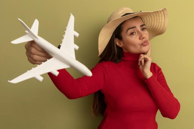 Pewna siebie ładna kobieta w kapeluszu plażowym trzyma model samolotu i kładzie palec na brodzie na białym tle na oliwkowej ścianie