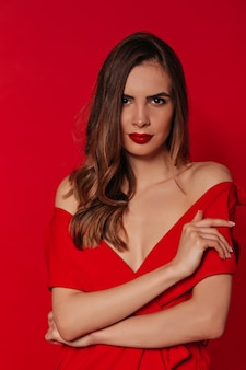 Pewna siebie ładna kobieta z falowanymi włosami na sobie czerwoną sukienkę z czerwonymi ustami na czerwonej ścianie