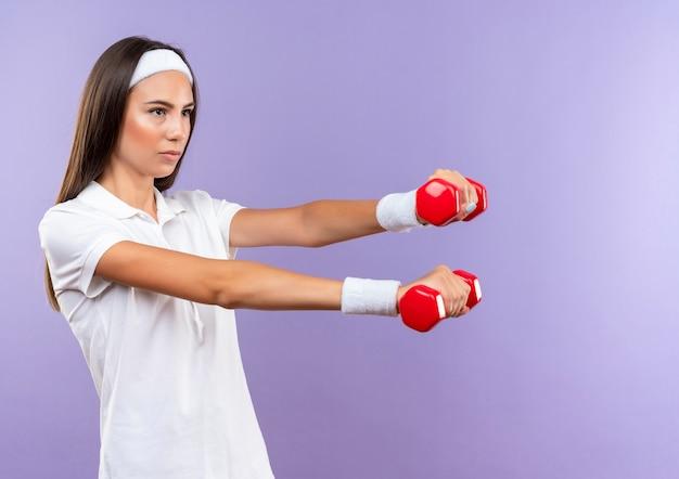 Pewna siebie, ładna sportowa dziewczyna nosząca opaskę na głowę i nadgarstek trzymająca hantle izolowane na fioletowej ścianie z miejscem na kopię