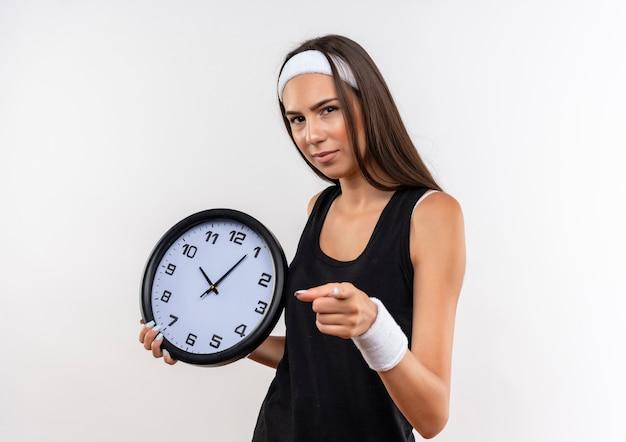 Pewna siebie, ładna sportowa dziewczyna nosząca opaskę na głowę i nadgarstek trzymająca zegar i wskazująca na białym tle na białej ścianie
