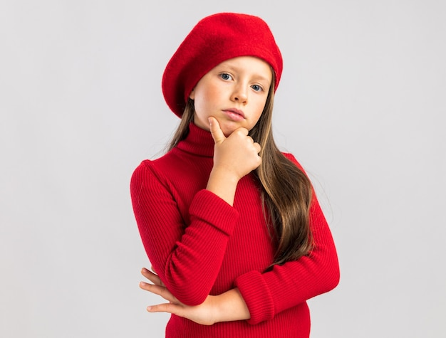 Pewna siebie mała blondynka w czerwonym berecie, trzymająca rękę na brodzie, patrząc na przód na białej ścianie z miejscem na kopię