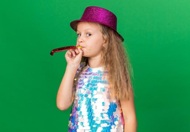 Pewna siebie mała blondynka w fioletowym kapeluszu imprezowym dmuchający gwizdek na zielonej ścianie z miejscem na kopię