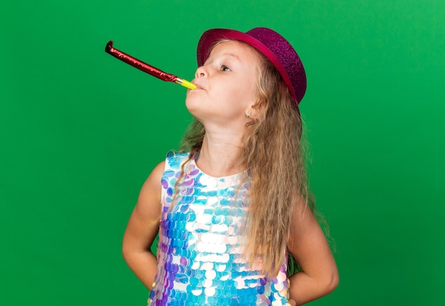 Pewna siebie mała blondynka w fioletowym kapeluszu imprezowym dmuchający gwizdek patrzący na bok odizolowany na zielonej ścianie z miejscem na kopię