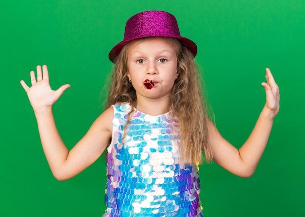 Pewna siebie mała blondynka w fioletowym kapeluszu imprezowym stojąca z uniesionymi rękami dmuchająca gwizdek imprezowy na zielonej ścianie z miejscem na kopię