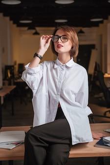 Pewna siebie młoda bizneswoman w okularach