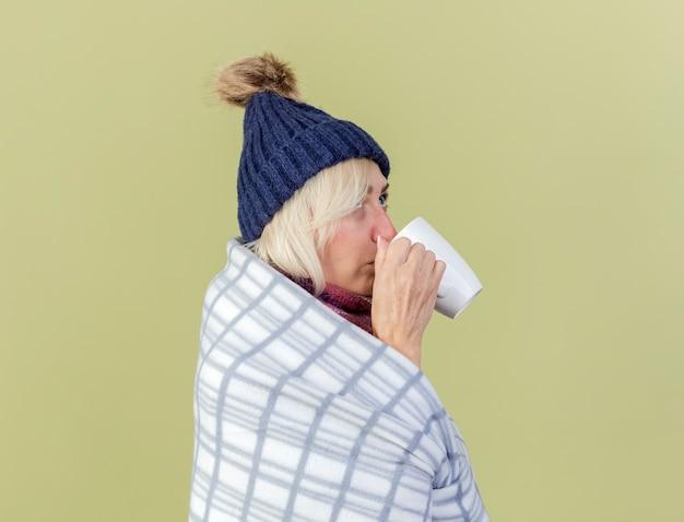Pewna siebie młoda blondynka chora słowiańska kobieta w czapce zimowej i szaliku owiniętym w kratę stoi bokiem i pije z kubka patrząc w górę odizolowane na oliwkowej ścianie z miejscem na kopię