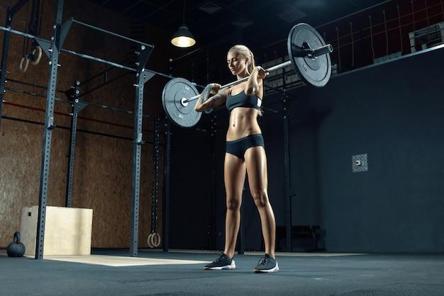 Pewna siebie młoda blondynka robi trening crossfit w siłowni