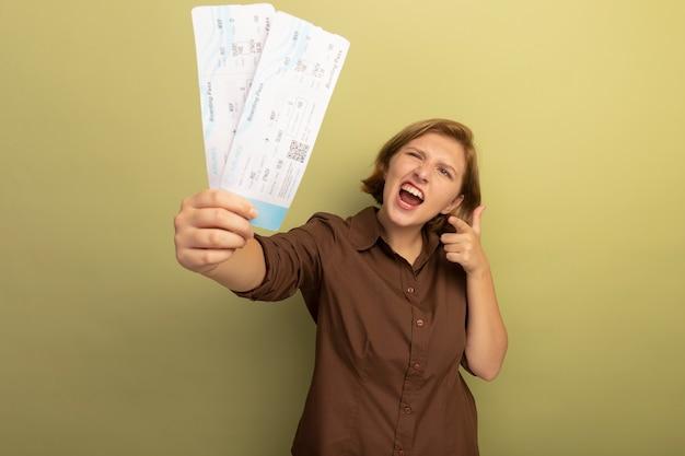 Pewna siebie młoda blondynka wyciąga bilety lotnicze, patrząc i wskazując na nie na oliwkowozielonej ścianie z miejscem na kopię